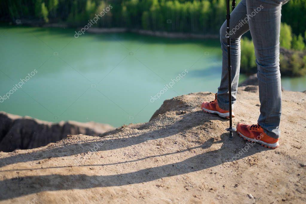 Photo of tourist with walking sticks next to mountain lake