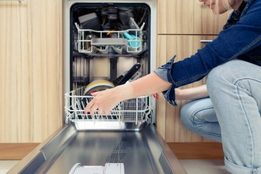 Photo of girl opening dishwasher with dirty dishes