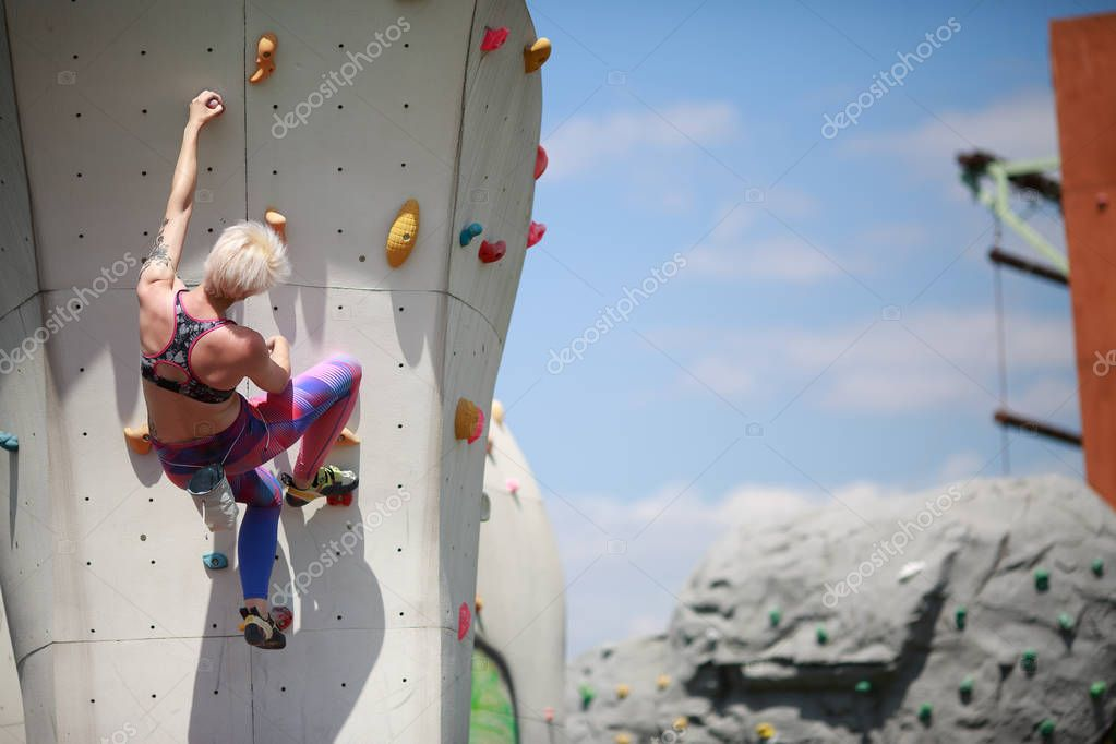 Photo from back of young blonde with short haircut in sports clothes practicing on wall for rock climbing against blue sky