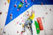 Photo from back of young ahtlete girl in sportswear scrambles on wall for climbing at workout
