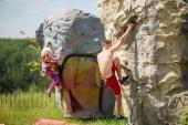 Fotografie Foto von Sportler in rote Shorts und Frau training auf Felsbrocken gegen blauen Himmel mit Wolken Klettern