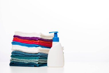 Photo of one bottle of liquid soap and colored towels on clean white background, place for inscription