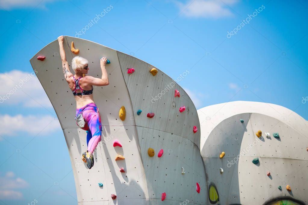 Photo from back of young athletic girl in leggings hanging on wall for climbing against blue sky