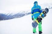 Foto von Mann mit Snowboard von hinten