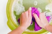 Fotografia Foto in cima ragazza hands vestiti di lavaggio rosa nel bacino verde con acqua schiuma sulla tabella bianca