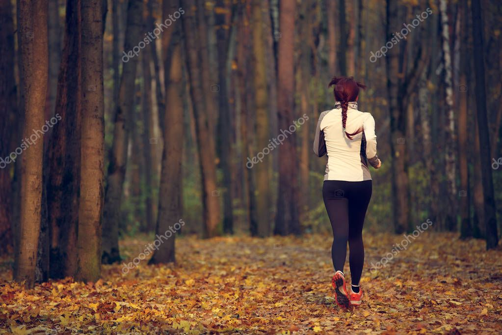 Photo from back of young sports girl running in forest