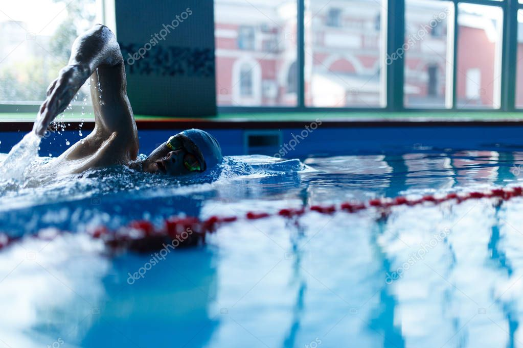 Photo of man swimming in pool indoors
