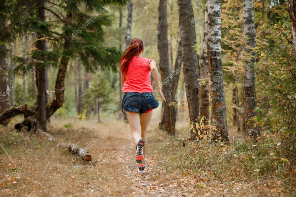 Photo from back of sportswoman running through forest