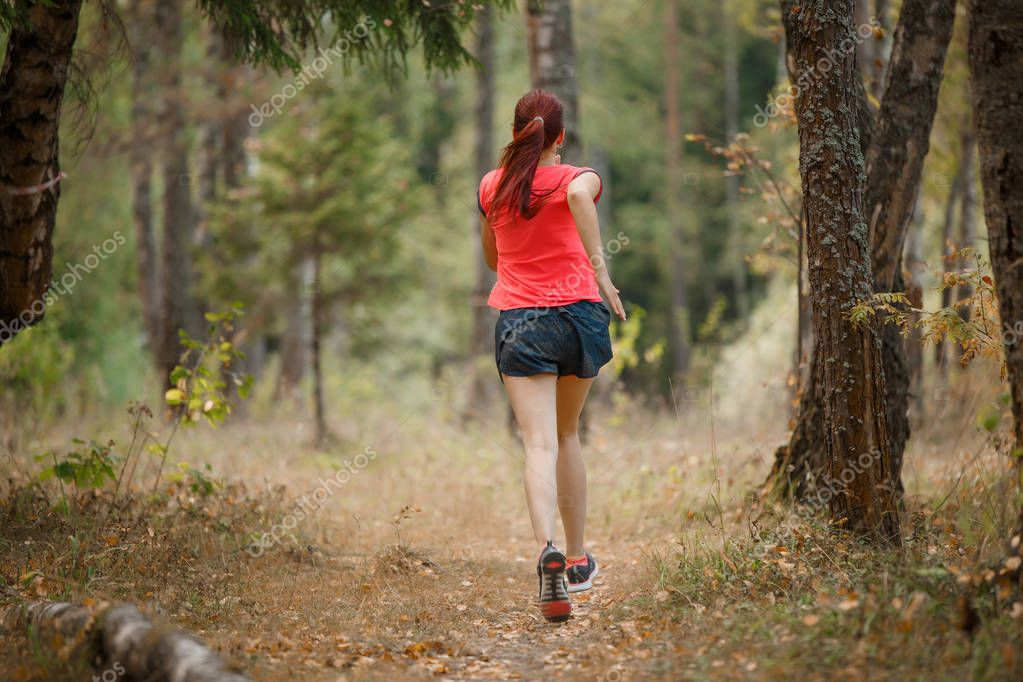 Image from back of sportswoman running through forest