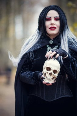 Picture of witch woman with skull in hands