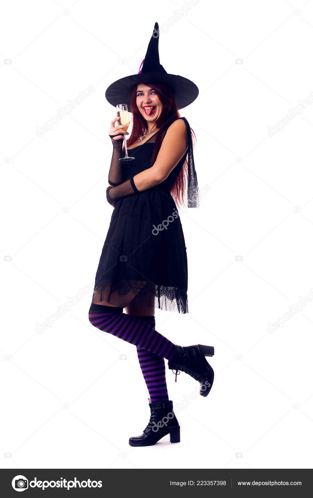 photo of smiling witch brunette in black dress and hat stock photo