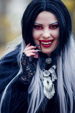 Image of smiling female vampire with stream of blood near mouth