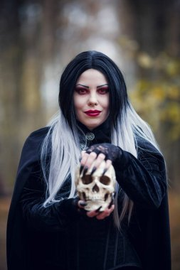 Image of witch woman in black cloak with skull