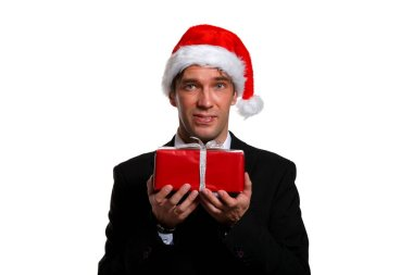 Image of young man in business suit, Santa cap with gifts in box