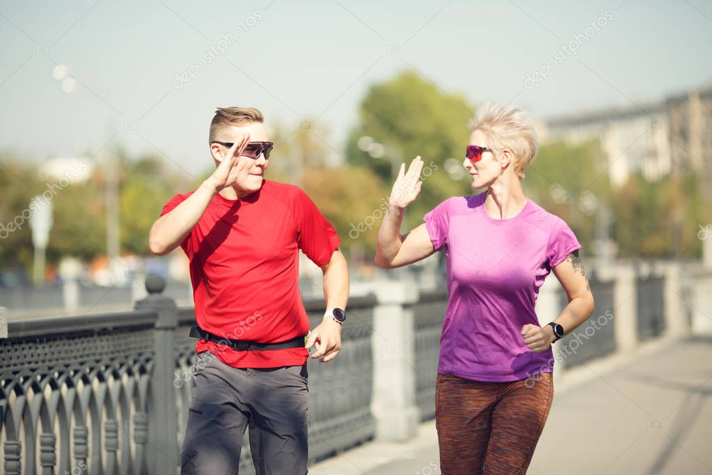 Photo of sports couple doing handshake running along embankment