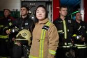 Portrét čtyř mužských a ženských hasičů na pozadí hasičský vůz