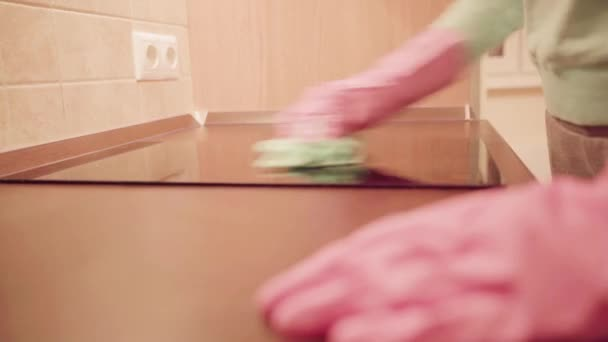 Closeup ženy ruce v růžové rukavice s hadrovou čištění kuchyňského stolu. Domácí práce a úklid koncepce