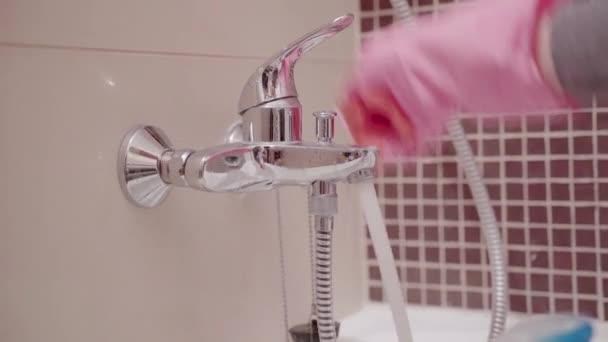 Közelkép a nő kezét gumikesztyűt, tisztítás fürdőszoba mosogató és csaptelep. Házimunka, takarítás koncepció.