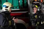 Foto strana dvou mužů hasič poblíž hasičský vůz