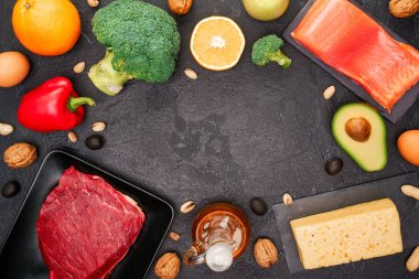 Image of food products on black stone table in studio.