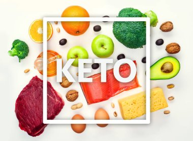 Picture on top of piece of meat, fish, cheese, eggs, vegetables, fruits, olives, walnuts on white background.Ingredients for ketogenic diet.