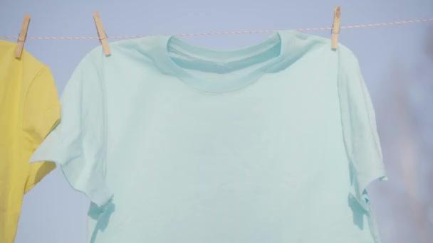 T-Shirts hängen an der Wäscheleine vor blauem Himmel