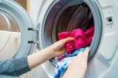 Női kezek üzembe piszkos ruhák mosógép