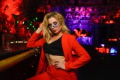 Foto einer blonden Frau in roter Jacke mit schwarzer Brille, die in der Nähe einer Bar in einem Nachtclub sitzt