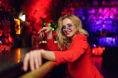 Photo of happy blonde with glasses and red suit sitting at bar with cocktail glass in nightclub