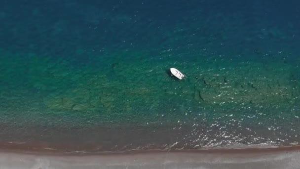 white alone boat drifts on sea water reflecting sunlight
