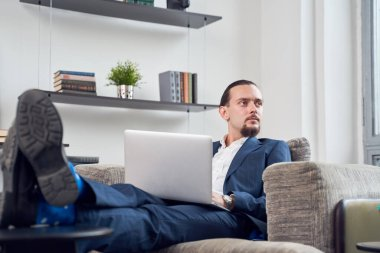 Image of serious businessman looking at side with laptop sitting on sofa in room.