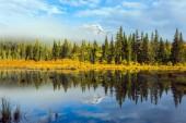 Fotografie Indian Summer in Jasper. Patricia Lake unter den Tannen und Kiefern. Das Wasser spiegelt die schneebedeckten Gipfel des Berges Pyramide. Das Konzept der Extreme und Ökotourismus