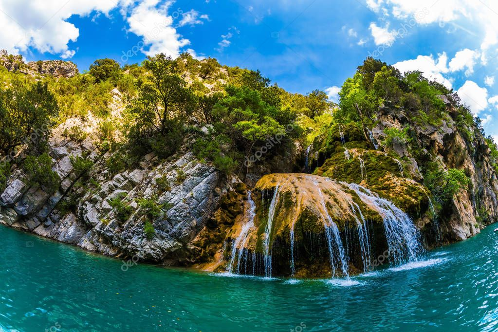 Charming little waterfall on limestone wall of Verdon Gorge, Provence Alps, France. Concept of ecological and active tourism
