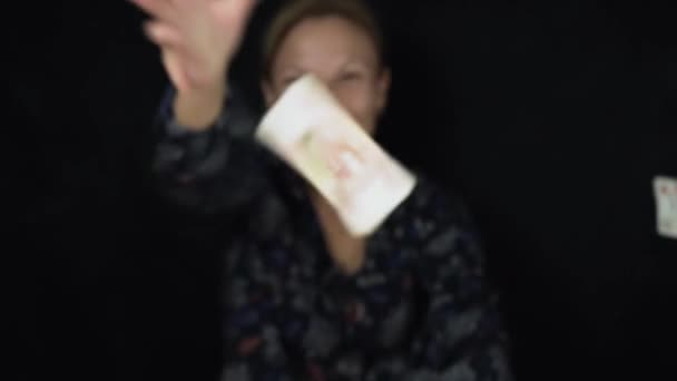 Enthusiastic woman throws banknotes five thousand rubles on black background, happy big pile of money slow motion stock footage video