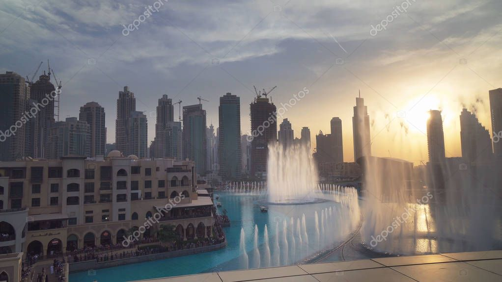 Dubai Fountain is the worlds largest choreographed fountain system on sunset background