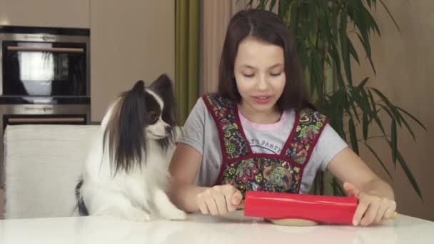 Dospívající dívka a pes Papillon připravit soubory cookie, kolejových těsta s váleček stopáže videa