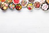 Fotografie Barevné sladkosti. Lízátka, makronky, marshmallow, marmelády a cukrovinky. Pohled shora s prostorem pro vaše pozdravy