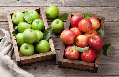 Ripe green and red apples in wooden box