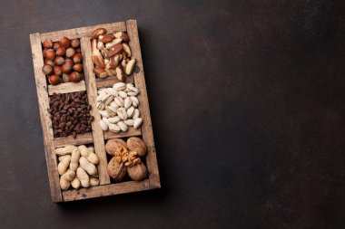 Various nuts selection: peanuts, hazelnuts, chestnuts, walnuts, pistachios and pecans in wooden box. Top view with space for your text