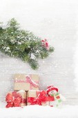 Christmas gift boxes, snowman toy and fir tree branch. View with space for your greetings