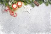 Vánoční dekorace, svíčky a větev stromu jedle věčným sněhem na kamenné pozadí. Pohled shora Vánoční pozadí s místem pro vaše pozdravy