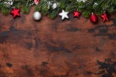 Christmas fir tree branch covered by snow and decor on wooden background. Top view xmas backdrop with space for your greetings