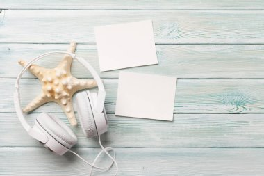 Travel vacation and music concept with headphones, starfish and photo frames on wooden backdrop. Top view with copy space. Flat lay