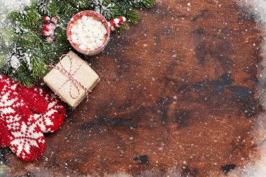 Christmas gift box, mittens, cup of hot chocolate with marshmallow and fir tree branch covered by snow on wooden background. Top view xmas backdrop with space for your greetings stock vector