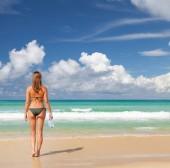 Mladá atraktivní žena odpočívat na pláži u moře. Světlý písek, modré nebe a křišťálově moře. Tropická pláž dovolená koncept. S kopií prostor