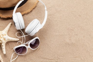 Travel vacation and music concept with headphones, sunglasses and starfish on sand backdrop. Top view with copy space. Flat lay