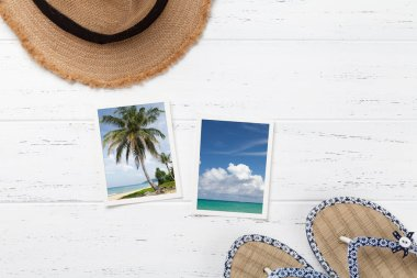Travel vacation background concept with beach hat, flip flops and summer photos on wooden table. Top view with copy space. Flat lay. All photos taken by me