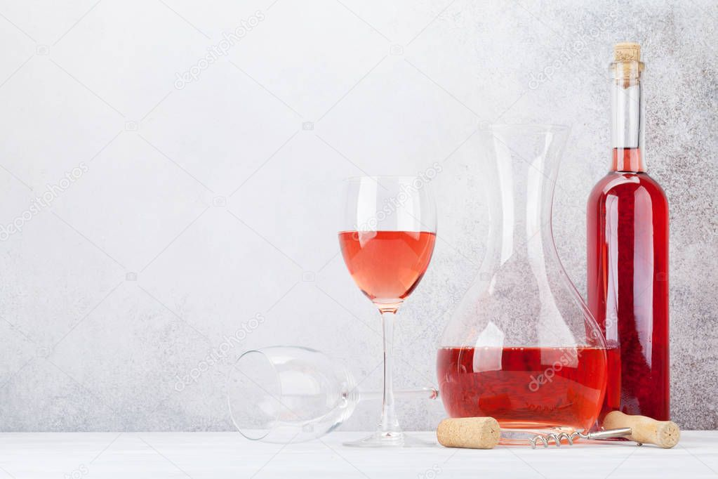 Rose wine in glass, bottle and decanter on stone background stock vector