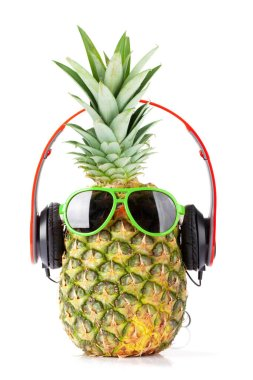 Ripe pineapple with sunglasses and headphones isolated on white background. Travel and vacation concept