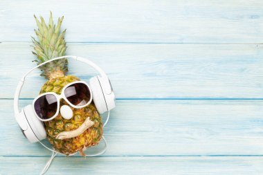 Ripe pineapple with sunglasses and headphones over blue wooden background. Travel and vacation concept. Top view flat lay with copy space